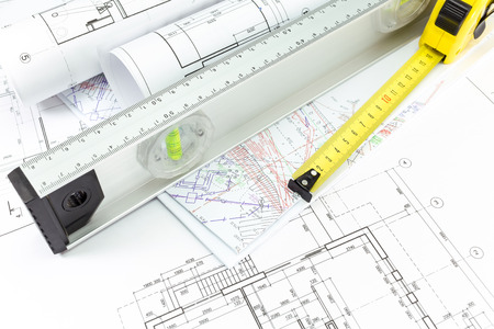 House building construction plans with spirit level and tape measure