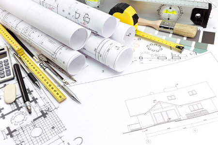 Architectural background with technical drawings and work tools photo