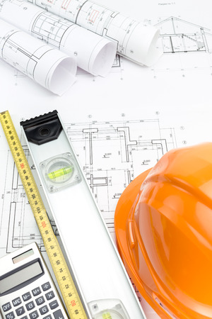 Safety helmet and tape measurement tools over architectural blueprint photo