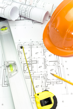 Construction plans with safety helmet and measurement tools