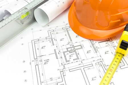 Safety orange helmet with level and tape measure over project drawings Stock Photo