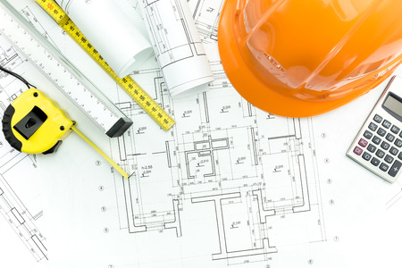 Construction plans with helmet and measurement tools on blueprints