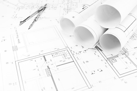 Architectural background with floor plans and rolls of technical drawings