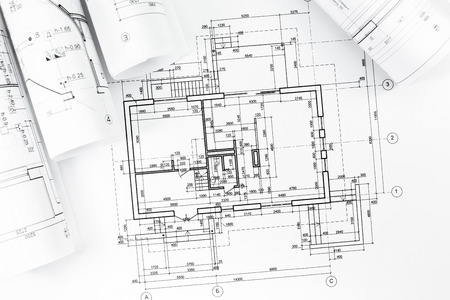 Architectonische achtergrond met plattegronden en rolde technische tekeningen Stockfoto