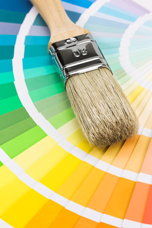 Brush for paint over color sample catalog. Closeup view. photo