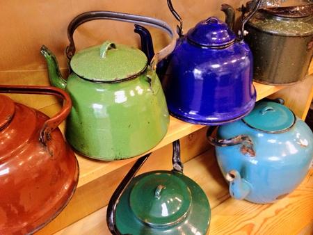 metallic: Shelf of cupboard with metallic enamel kettles