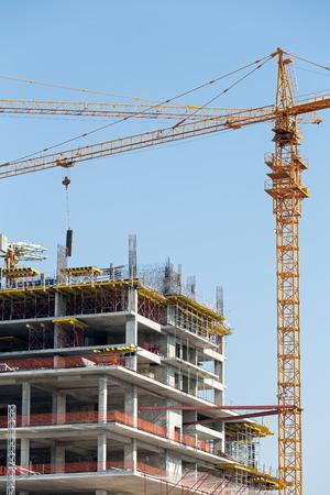 grue  tour: Immeuble en construction et la grue � tour contre le ciel bleu