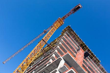 grue  tour: Chantier de construction avec la tour grue jaune contre le ciel bleu fonc�