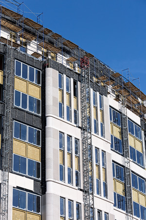 Incomplete modern building under construction with scaffolding photo