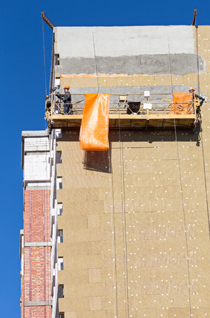 rock wool: Construction workers plastering facade of high-rise building Stock Photo