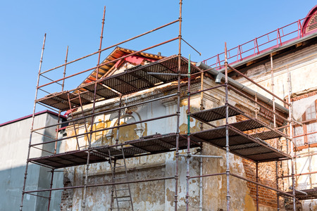 Scaffolding covering a facade of an old building  under restoration