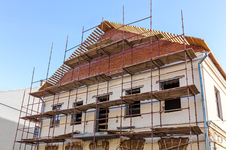 Old historic building facade under reconstruction with scaffolding photo