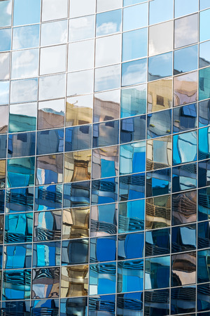 mirrored: Glass wall of modern high-rise building with reflections