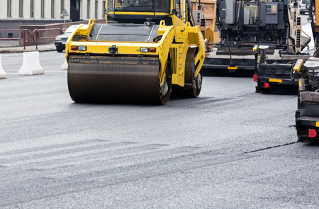 roller compactor: Steam roller machines compacting fresh asphalt during road repairing
