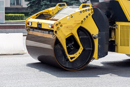 Compaction of asphalt surface by vibratory rollers machines during road construction works photo