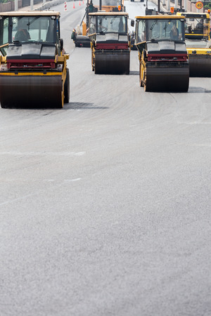 compacting: Steam rollers machines compacting fresh asphalt during road construction works Stock Photo