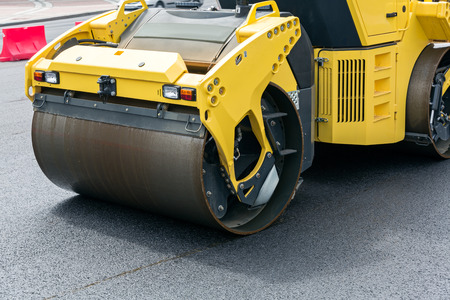 Heavy steam rollers compacting fresh layer of asphalt photo