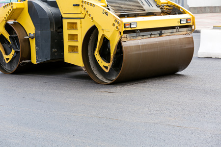 roller compactor: Heavy yellow roller compactor asphalting the street road Stock Photo
