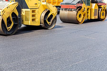 compacting: Steam road rollers compacting fresh asphalt during road repairing works