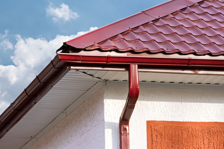 House roof, gutters and downspout on the corner of a house Stock Photo