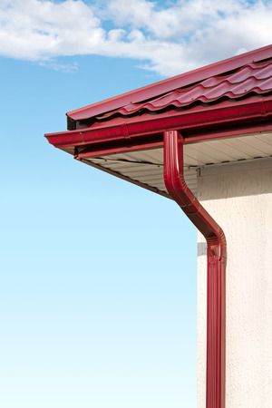 Guttering and drainpipe on house. Architecture detail on home.