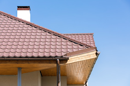 overhang: Corner of a house with gutter and tiled roof
