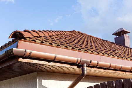 chimney corner: Red roof tile with chimney and cloudy sky  Stock Photo