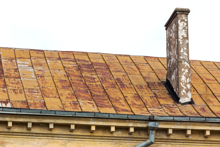 Old rusty metal corrugated roof with chimney photo
