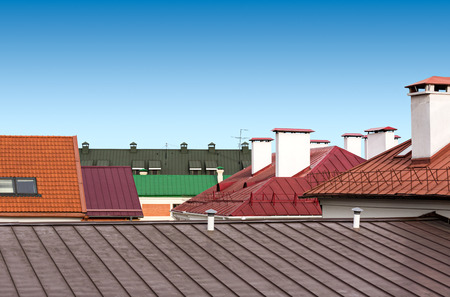 Cityscape with red tile roof, chimney, windows and gutter against sky