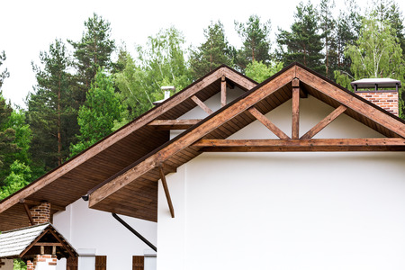 rafters: Gable of new house with roof rafters and brick chimney Stock Photo