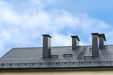New metal tiled roof with chimney against the blue sky