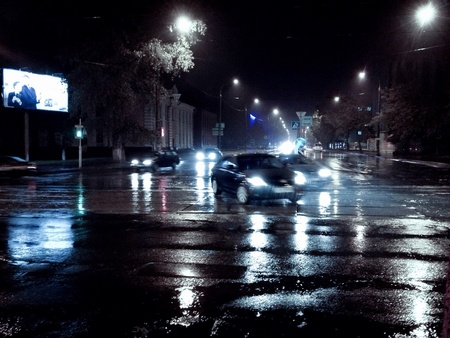都市の夜に濡れた道路上の車