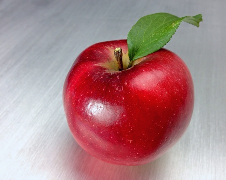shiny metal: Red apple on brushed metal