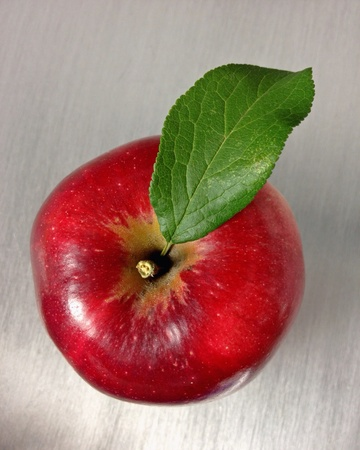 shiny metal: Red apple with green leaf