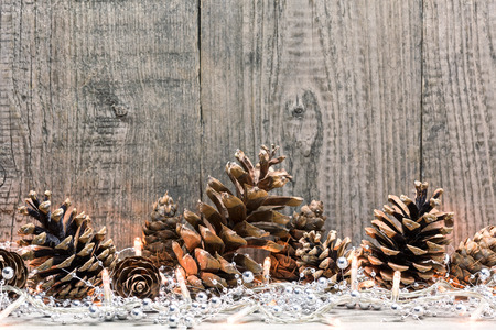Christmas decoration with lighs and fir cones on wooden background