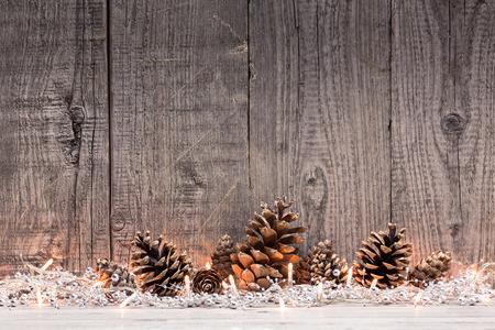 feriado: Decoración de Navidad con lighs y piñas con fondo de madera natural,