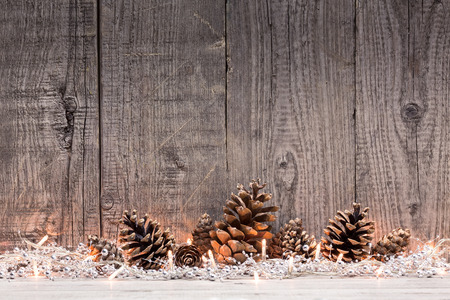 Christmas decoration with lighs and fir cones with natural wooden background Archivio Fotografico