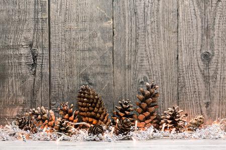 나무 배경 위에 크리스마스 조명과 콘 휴일 장식 스톡 콘텐츠