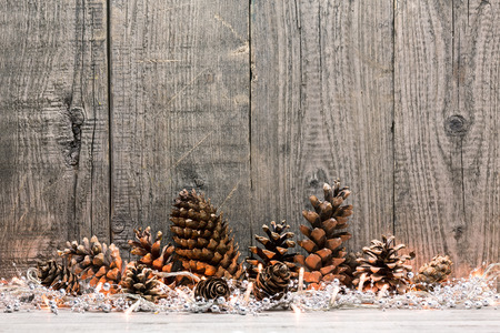 Holiday decoration with Christmas lights and cones over wooden background