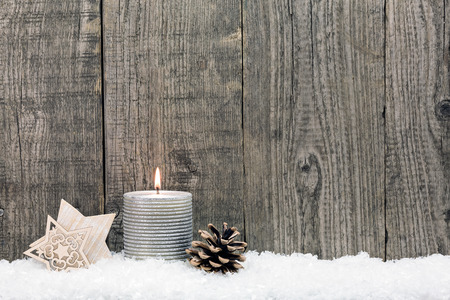 Christmas background with candle, stars and pine cone on snow