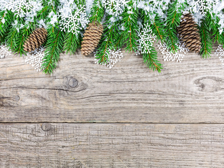 Christmas fir tree covered with snow on wooden board background photo