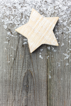 Handmade rustic Christmas star with snowflakes on old textured wooden board photo