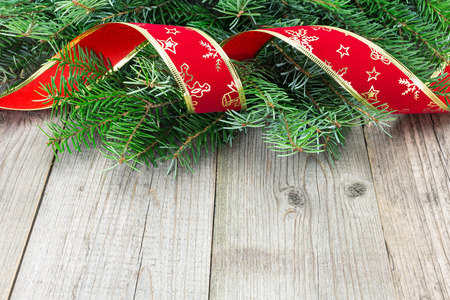 Christmas background with fir and red ribbon on a wooden board photo