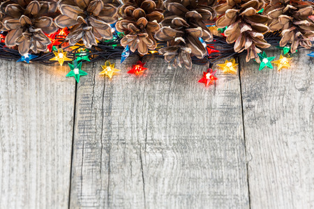 Christmas decoration with fir cones and lights on weathered wooden boards photo