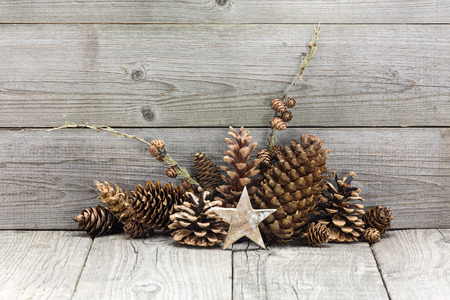 Holiday decoration with Christmas star and cones over wooden background photo