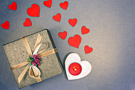 Valentine gift box with golden ribbon, red hearts and burning candle photo