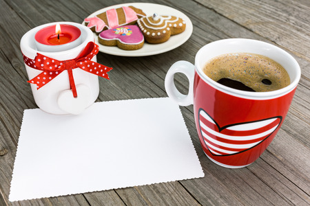 Cup of coffee with creamy foam with a candle, cookies and greeting card photo