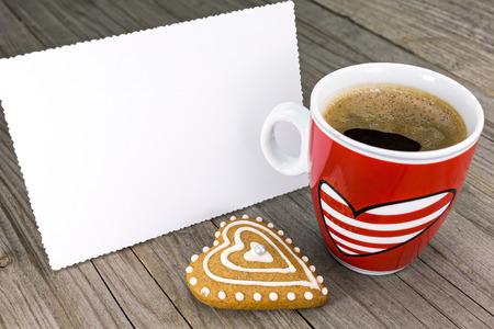 Red cup of coffee and heart shape cookie with blank valentines greeting card on wooden table photo