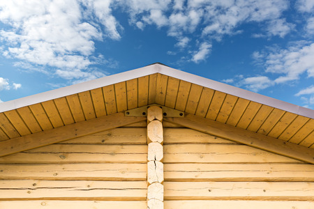 Wooden roof gable with log wall against cloudy sky photo