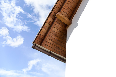 rafters: Roof with rafters and plaster wall of house against cloudy sky Stock Photo